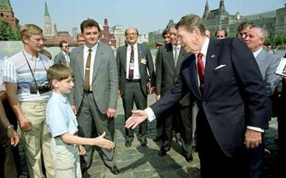 Vladimir Putin (far left) as a young KGB spy, meeting Ronald Reagan.